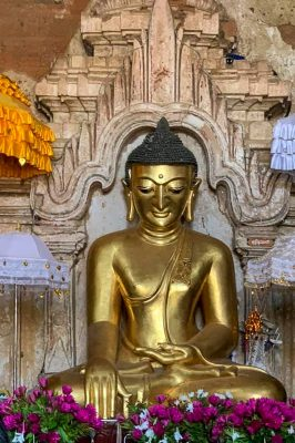 Golden Buddha Statue in Myanmar With Lilac Flowers