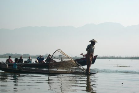 One Leg Rower On The Inle Lake With Tourist Boat